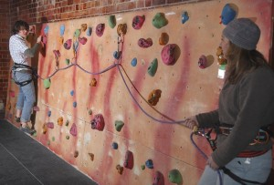 Practising belaying a lead climber close to the ground on an easy traverse in a bouldering wall. This is more about the belayer learning to belay, although the climber can also practice clipping the bolts.